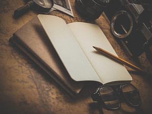 brown pencil on white book beside black eyeglasses