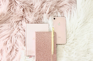 gold iPhone 8 beside book