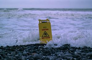 caution wet floor signage on gray rocks in seashore