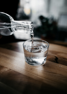 person holding bottle pouring water on drinking glass