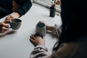 woman in black long sleeve shirt holding black ceramic mug